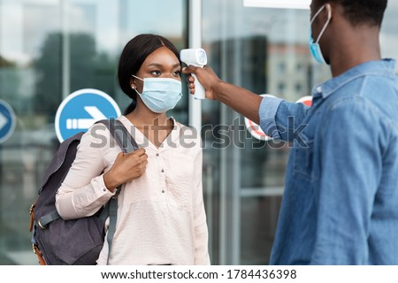 Airport Worker Checking Black Female Passenger's Temperature With Electronic Thermometer After Arrival, Covid-19 Outbreak Prevention Royalty-Free Stock Photo #1784436398