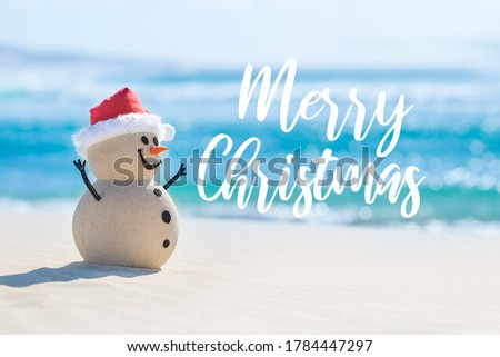 Sandy Christmas Snowman is celebrating Christmas on a beautiful beach with Merry Christmas wishes in the background Royalty-Free Stock Photo #1784447297