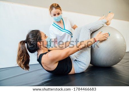 Caucasian female physical therapy professional at a clinic giving a pilates lift treatment with a therapy ball to a client with a face mask due to the covid 19 coronavirus pandemic. #1784466683