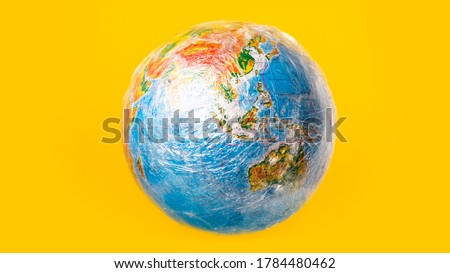 World ocean pollution and planet ecology concept. The globe is wrapped in plastic Royalty-Free Stock Photo #1784480462