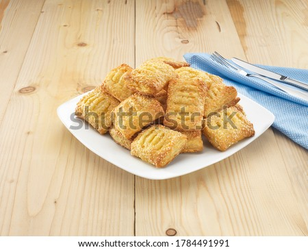 Puff pastry with potatoes and sesame on the white plate. A traditional Turkish pastry, puf borek. Greek pastry with feta, goat, spinach or meat. With cloth napkin, fork and knife on wooden floor. #1784491991