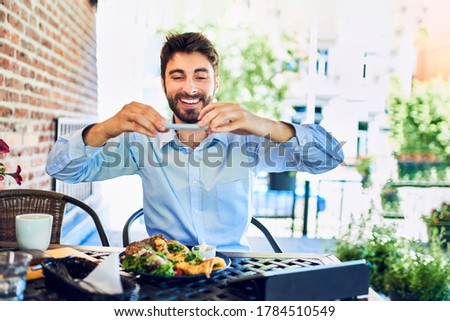 Portrait of happy young man taking picture of breakfast in cafe outdoors