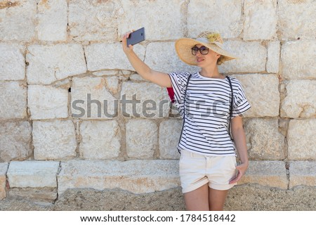 Beautiful young female tourist woman wearing big straw hat, taking self portrait selfie, standing in front of old textured stone wall at old Mediterranean town.