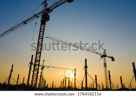 New construction site with cranes on orange sunset, sunrise sky background. Steel frame structure, structural steel beam build large buildings at construction site . construction machinery. #1784582156
