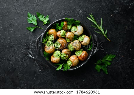 """""""Escargots de Bourgogne"""" - baked snails with garlic, butter and basil. French traditional food. Top view. Free space for your text. Royalty-Free Stock Photo #1784620961"""