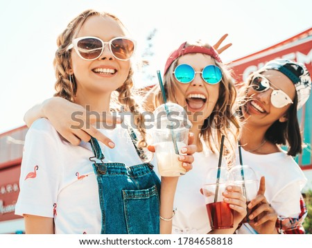 Three young beautiful smiling hipster girls in trendy summer clothes.Sexy carefree women posing outdoors.Positive models holding and drinking fresh cocktail smoothie drink in plastic cup with straw #1784658818