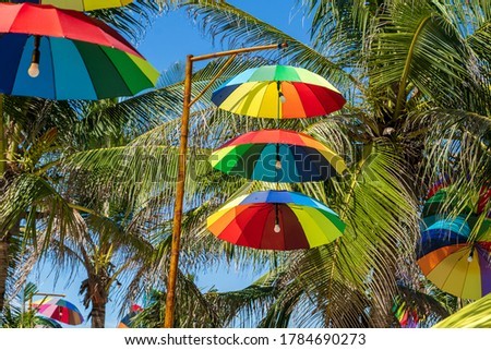 Street lamps decorated with colorful umbrellas hang on a pillar in street against the blue sky and green coconut palm tree on a sunny day, Vietnam #1784690273