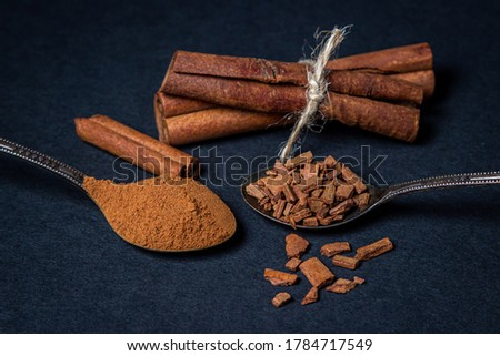 Cinnamon on a black background. A spoonful of young cinnamon lies next to a spoonful of crushed cinnamon. behind two sticks of cinnamon tied with a jute thread. #1784717549