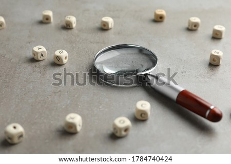 Magnifier glass and cubes with letters on light grey stone background, closeup. Find keywords concept