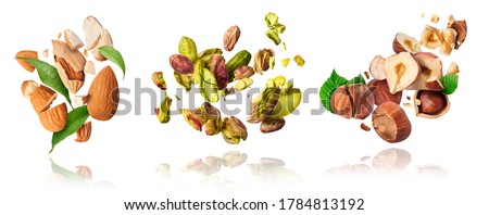 A set with Flying in air fresh raw whole and cracked pistachios, almonds and hazelnut isolated on white background. Concept of Pistachios almonds and hazelnut is torn to pieces close-up.  #1784813192