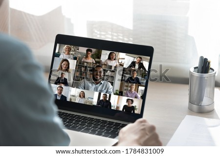 Back view of male employee have online video call on laptop with diverse multiethnic colleagues, man worker involved in webcam conference or virtual event on computer with multiracial businesspeople #1784831009