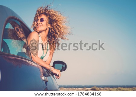 Attractive curly blonde young woman smile and enjoy the wind outside the car - concept of beauty and travel for happy and cheerful caucasian people - alternative lifestyle female feel the freedom joy Royalty-Free Stock Photo #1784834168