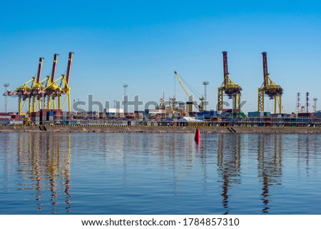 Seaport. Water, port cranes and containers under a blue sky. Cargo transportation by water. Merchant fleet. Panorama of the port on a Sunny day. #1784857310