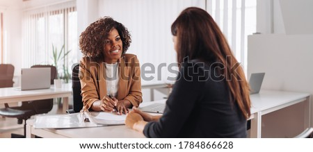 Woman consulting with a female financial manager at the bank Royalty-Free Stock Photo #1784866628