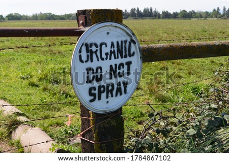 An organic farming sign.  Bold text and a wooded fence are visible.
