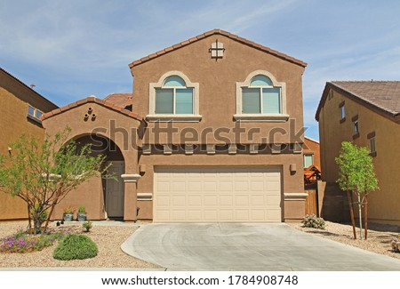 New two-story, brown and beige stucco home in Tucson, Arizona, USA with beautiful blue sky and landscaping.   Royalty-Free Stock Photo #1784908748