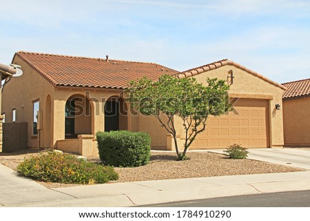 New ranch, gold and mustard yellow stucco home in Tucson, Arizona, USA with beautiful blue sky and landscaping. Royalty-Free Stock Photo #1784910290