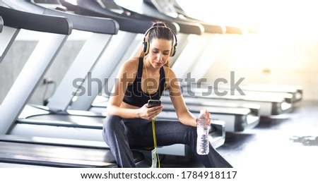 Woman athlete taking rest and listen to music on mobile phone after running on treadmill machine at gym sports club. Fitness Healthy lifestye and workout at gym concept.