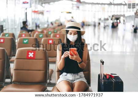 Airport terminal social distancing chair form corona virus pandemic. Young adult tourist woman sitting wear mask protect from covid 19. People travel with new normal lifestyle concept. #1784971937