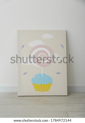 Adorable picture of cupcake and lollipop on floor near white wall. Children's room interior