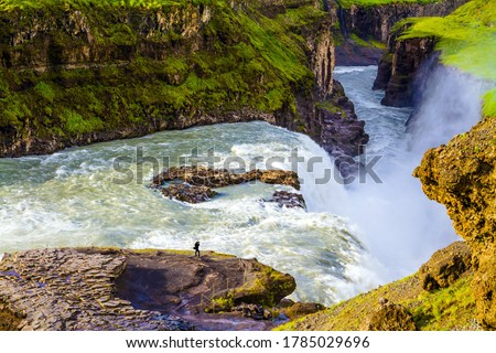 """Iceland. Tourist with a photo bag takes pictures of a bubbling waterfall. Gullfoss """"Golden Falls"""" - the waterfall fed by thawed glacial water. The concept of extreme and photo tourism"""