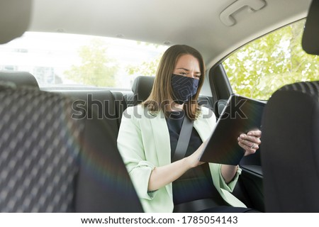 A girl in business clothes is sitting in the back seat of a car with a protective mask on her face and holding a tablet. Work on the way to the office #1785054143