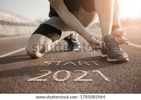2021 symbolises the start into the new year.Start of people running on street,with sunset light.Goal of Success Royalty-Free Stock Photo #1785085964
