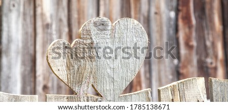 Heart shape in a wooden fence. Rustic background with hearts carved in wood. heart Shaped fence boards. heart wood shape, wooden rustic fence. Country summer house decor, natural wood material.