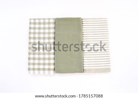 Top view new kitchen towels in green olives strip and white color simple pattern in differnet style on white background .Equipment necessary  in kithchen for wippe things.