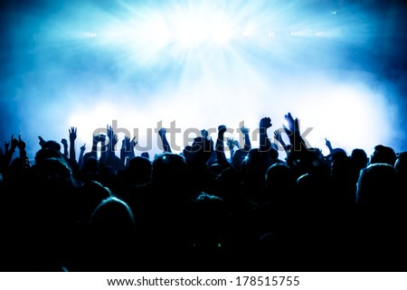 silhouettes of concert crowd in front of bright stage lights #178515755