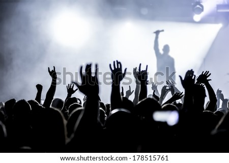 silhouettes of concert crowd in front of bright stage lights #178515761