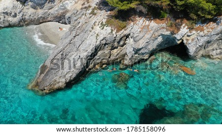 Aerial drone photo of secluded rocky cove near turquoise pebble paradise beach of Kastani covered with pine trees, Skopelos island, Sporades, Greece