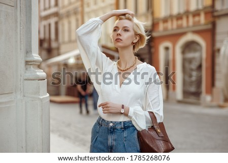 Street style photo of elegant fashionable woman wearing trendy white blouse, high waist jeans, wrist watch, with brown faux croco leather textured bag. Model walking in street of European city  #1785268076