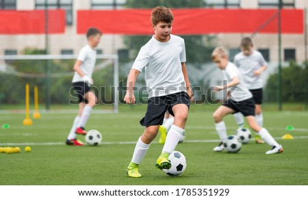 Children kicking soccer balls on artificial grass training field. Young boy leading ball and improving dribbling skills. Physical education class on school training pitch Royalty-Free Stock Photo #1785351929