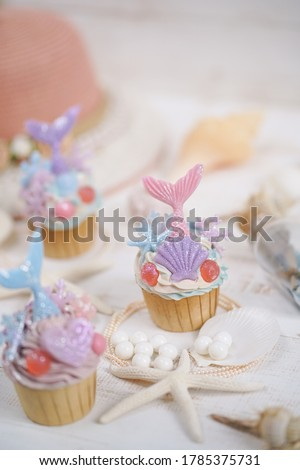 Mermaid cupcake. Freshly made cupcake in fantasy fairy tales concept of mermaid, pastel theme in blue, purple and pink on white wood background.