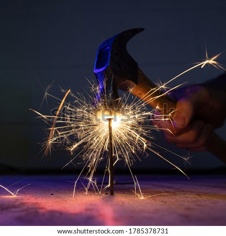 A hammer strikes a nail with bright sparks and fire. Royalty-Free Stock Photo #1785378731