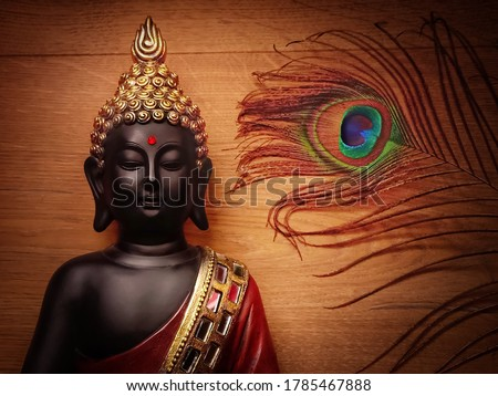 Buddha statue with wooden background and peacock feather/wallpaper image with peacock feather and smiling buddha/peaceful image of buddha meditating with wooden backdrop #1785467888