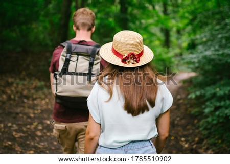Couple holding hands walking in forest, back view. Adventure, travel, tourism, hike, people. Rear view of two people carrying backpack while walking through wood. Man holds girlfriend by hand on hike. #1785510902