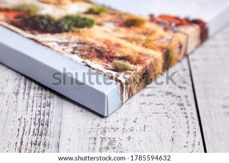 Canvas print on wooden background. Wrapped canvas, edge, corner, closeup. Detail of stretched landscape photography with gallery wrapping. Photo printed on canvas Royalty-Free Stock Photo #1785594632