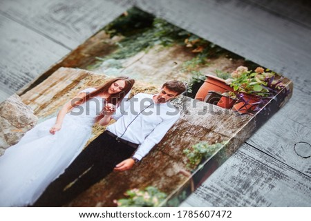 Canvas print. Photo printed on canvas. Sample of stretched wedding photography with gallery wrap, side view, closeup. Portrait on grey wooden surface Royalty-Free Stock Photo #1785607472