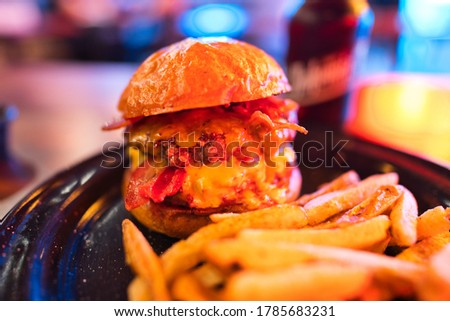 Picture of a double bacon cheese burger with a shallow depth of field under neon lights from the wall.