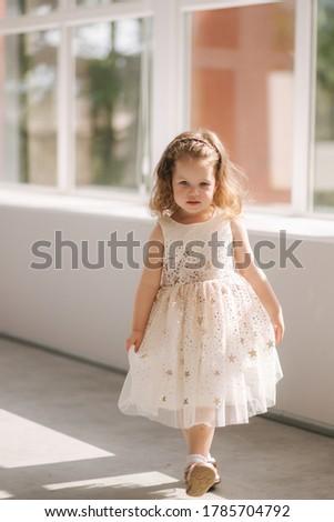 Cute little girl three year old in dress posing for photograper in studio. Beutiful little girl dance