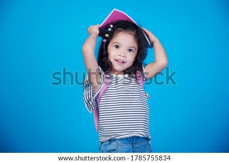 portrait of little girl schoolgirl on blue background.Copy space.