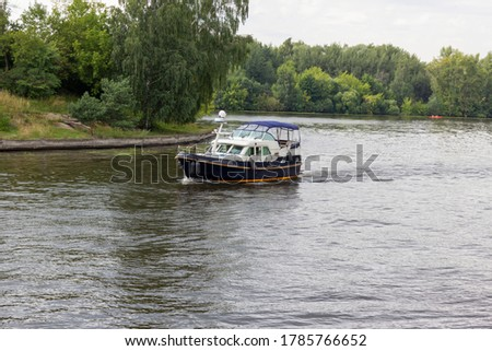 Blue boat floating on the river. Trees grow on the banks of the river. Fork of the river. Landscape, summer day. Water excursions and trips.