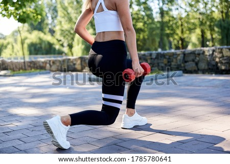 Young blond woman, wearing white top and black leggings,doing power exercises in park in summer.Training process outdoors. Close-up picture of female legs, doing lunges, holding red fitness weights.