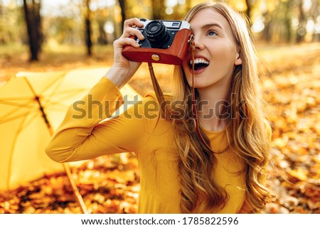 happy smiling young woman in autumn Park sitting on blanket posing with retro camera taking pictures enjoying warm autumn weather