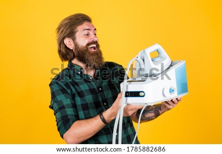 All you need is iron. man ironing at home. Happy Man Ironing Clothes. man concentrated on ironing a shirt. laundry room at home. Clothes ironing board household concept. domestic everyday duty. #1785882686