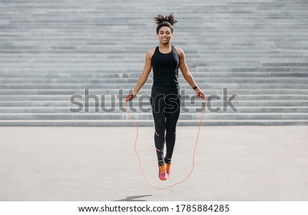 Female athlete does cardio workout. Smiling african american girl in sportswear with fitness tracker jumping rope outdoors, free space Royalty-Free Stock Photo #1785884285