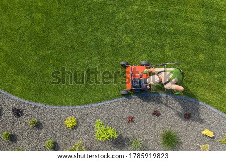 Powerful Gasoline Lawn Aerator Job For Controlling Lawn Thatch, And Reducing Soil Compaction. Backyard Grass Field Maintenance. Caucasian Gardener in His 40s. Aerial View. Royalty-Free Stock Photo #1785919823