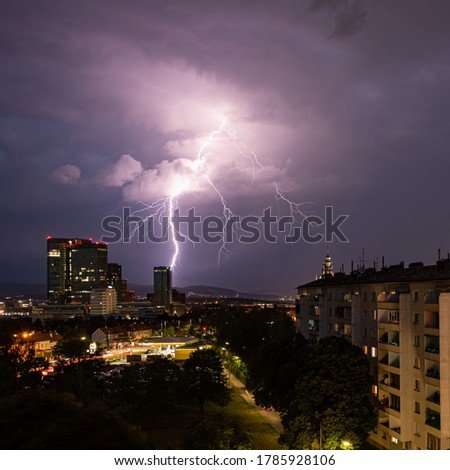 Violent summer thunderstorm with enormous lightning over the Wienerberg City in Vienna with construction cranes on the right side of the picture